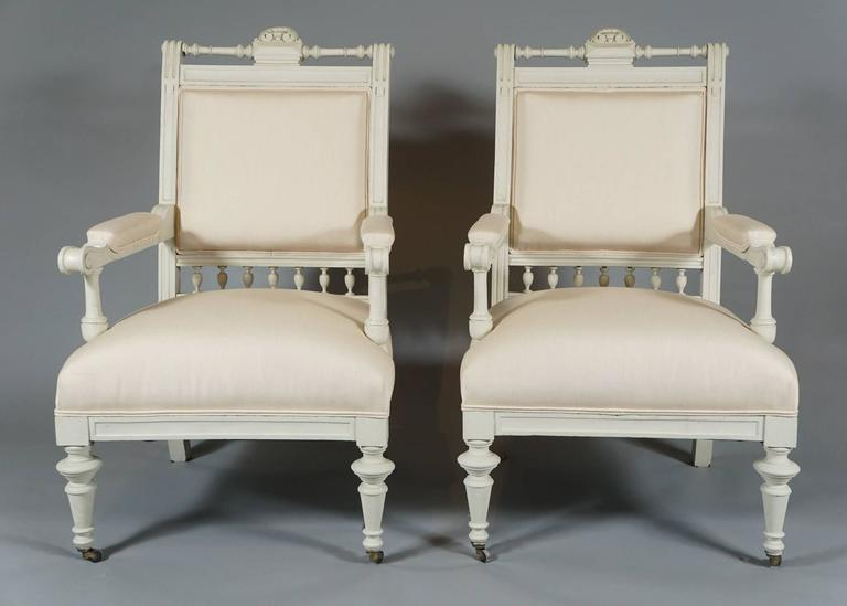 Handsome pair of armchairs from the Aesthetic Movement, circa 1880s, in white-painted wood with turned legs and spindle decoration reupholstered in white linen/cotton, front legs on castors.