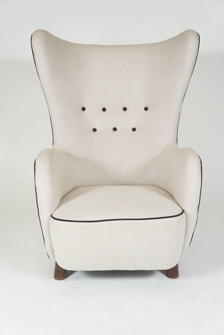 Wingback lounge chair by Mogens Lassen from Denmark, 1930s covered in white linen with black piping and buttoning.