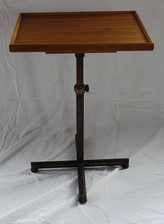 Swiss made adjustable height side table. There are two attached separate tops. They spin to cover each other into a single tabletop. The large top measures: 21 x 16. The smaller top measures: 11 x 11. The base can extend to a minimum height of 26
