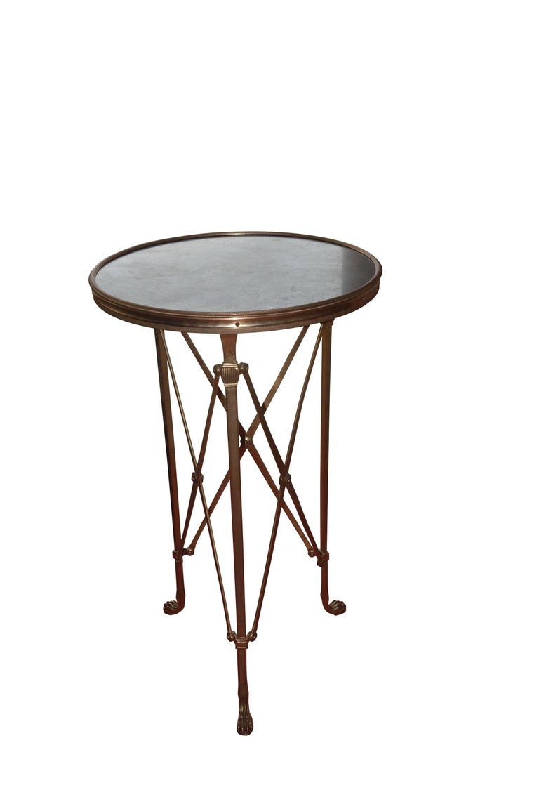 1970s French classic round honed black marble top with bronze base campaign gueridon. Claw foot details. X frame base. Two available.