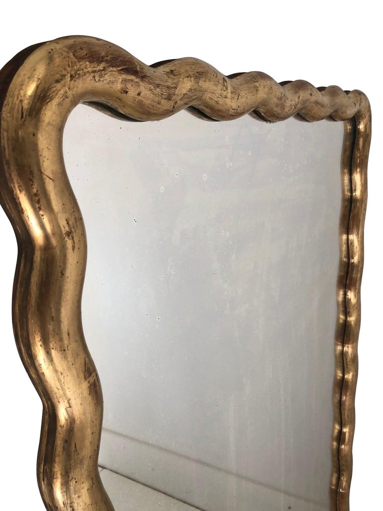 Newly restored classic gold gilt leaf serpentine shaped 19th century French mirror.