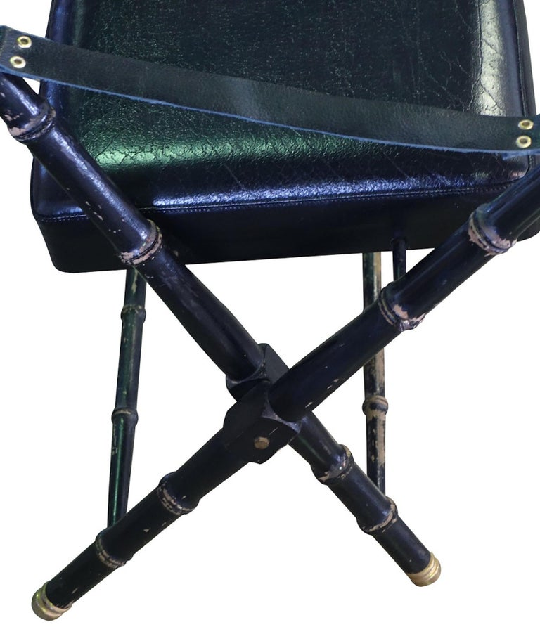 Midcentury French Maison Jansen black leather campaign chair. Brass details. Faux bamboo decorative details.