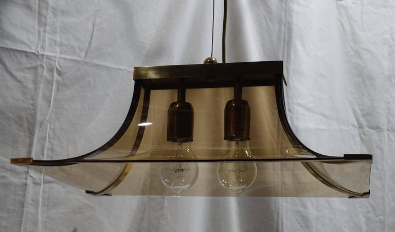1970s Italian smoked taupe glass curved chandelier. The chandelier has two brass sockets and brass strips trimming the edges and corners. Recently rewired. Ceiling cap is included. The chandelier is in excellent condition.