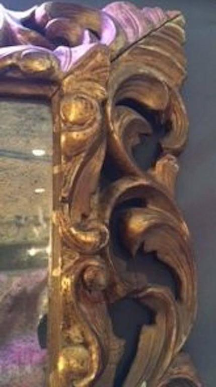 French ornately carved wood gold gilt framed mirror, circa 1830.