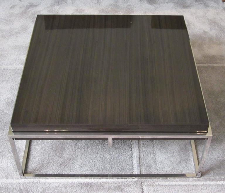 Contemporary Belgian square coffee table. Polished stainless cube base with laminated grey Awari wood top.