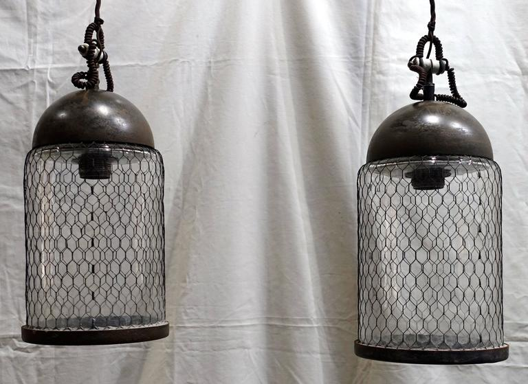 Contemporary Italian pair of elongated brushed pendant lights with cage around glass. Brushed metal dome.