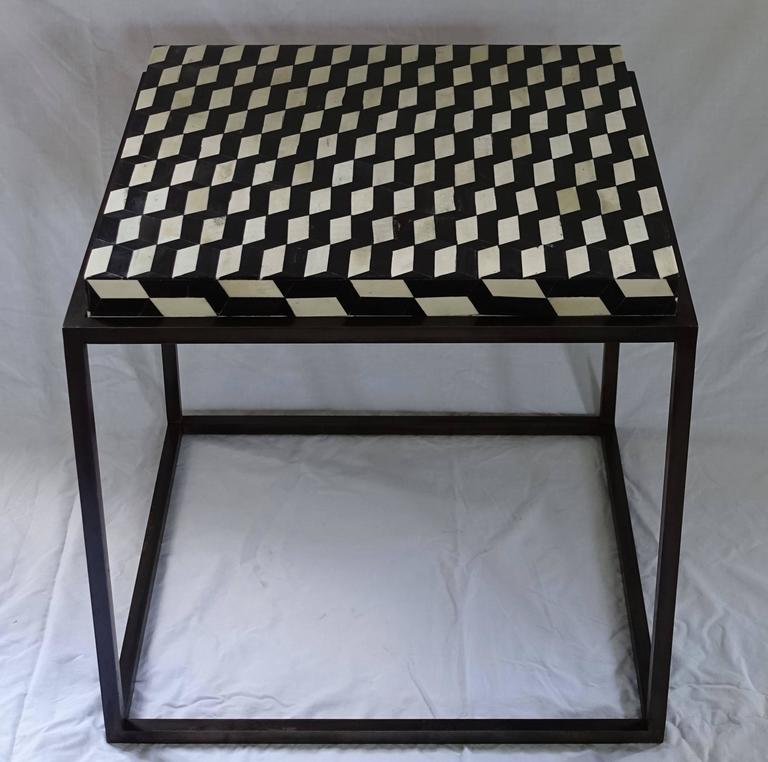 Contemporary side table with a black and white faux bone top on a custom steel base.