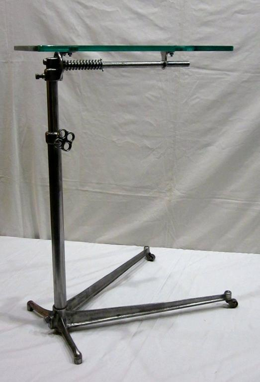 1940s English glass top adjustable hi low, polished steel base side table. Thin V-base on original casters. Top: 18