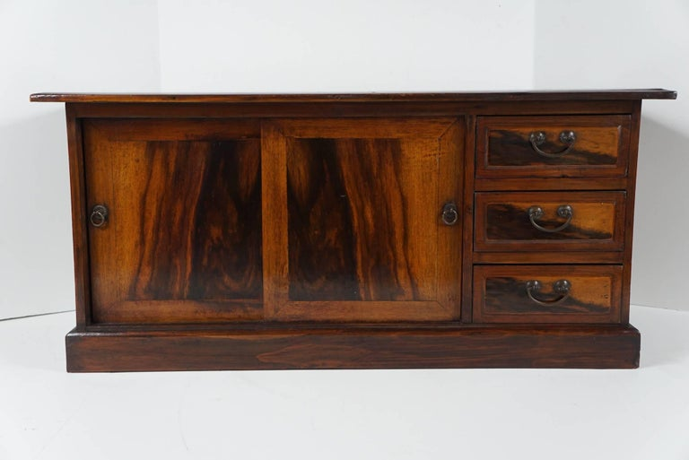 This small cabinet is made with a great deal of attention to it's visual appeal and the placement of the woods selected. Crafted in 1890-1900 a time of great social and political change in Japan this cabinets speaks volumes about the cultures goals
