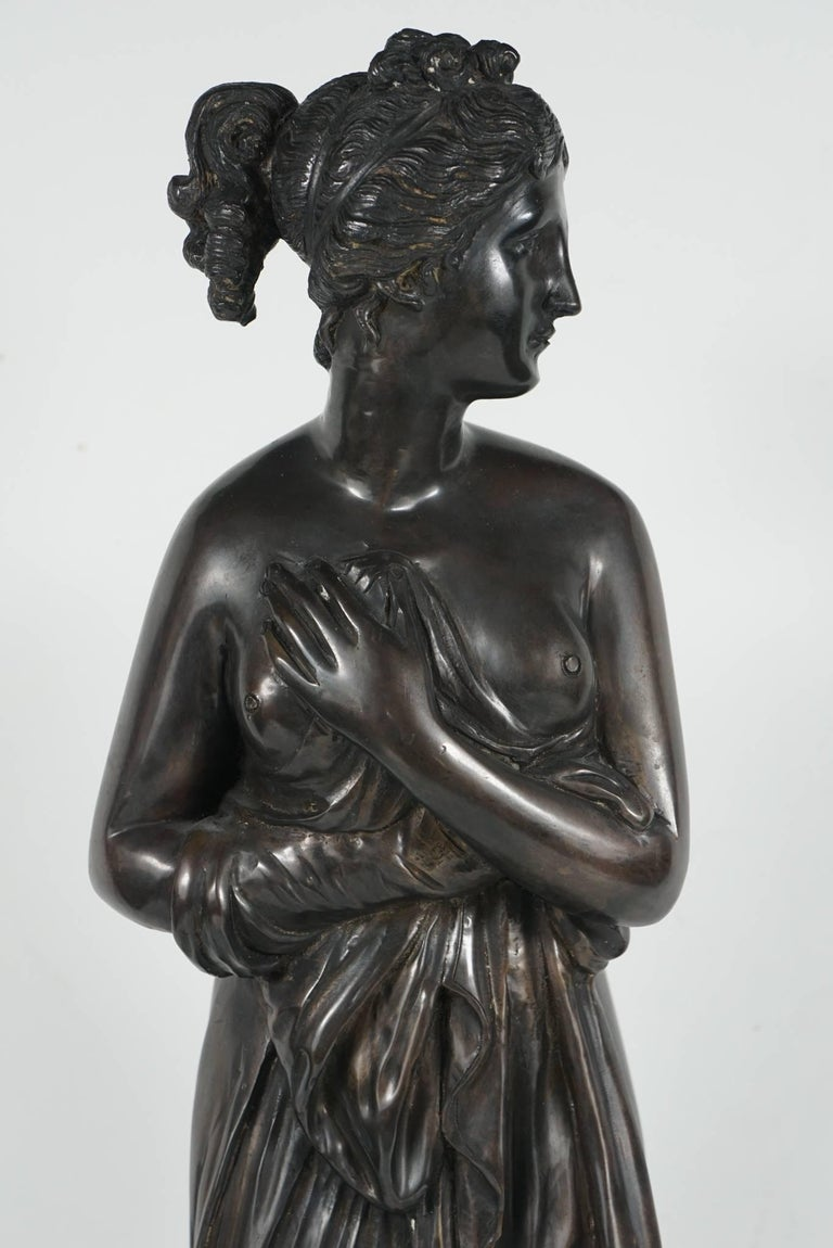 The piece is Italian and was made circa 1890 to 1900. The figure of a classically draped nude Venus stands holding a loose garment across her front but revealing her breasts and buttocks. She stands next to a footed jewelry casket decorated in