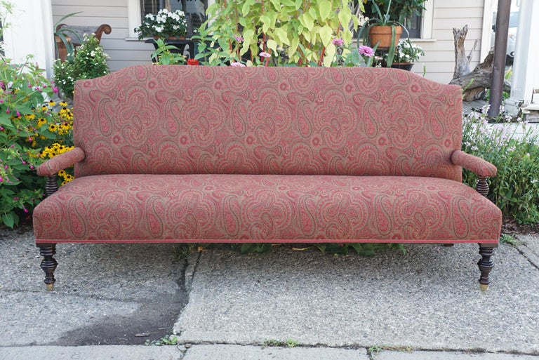 This large vintage Edwardian style sofa made in the 20th century is crafted from mahogany and features ring turned arm supports with matching front legs terminating in large brass sabots The high back and deep seat makes for easy relaxing and casual