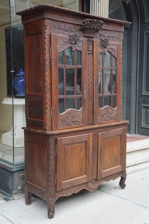 This nice and compact sized buffet with glazed doors comes from the Normandy region in France and was made, circa 1770 during the rein of Louis XV. Created using dark stained oak a difficult wood to carve the piece is centered on its carved and