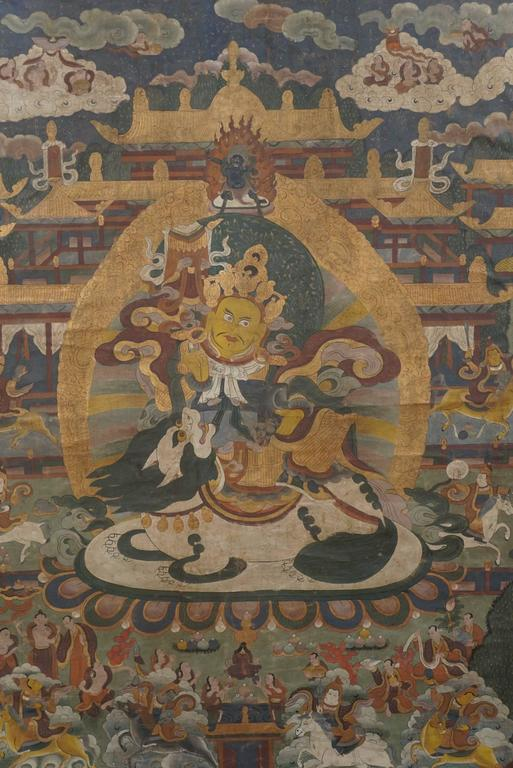 This fine vintage painted work is richly filled with small figures surrounding a large central figure. All interspersed with clouds and religious symbols. The colors are deep but muted with time and age. The piece is newly bordered in rich Chinese