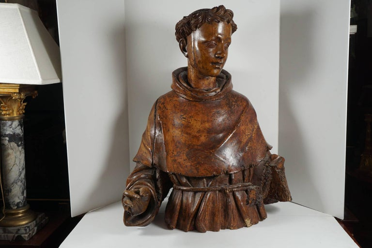 This very fine bust carved in walnut was originally full size and over the years has been cut down to waist height. The color of the wood is rich and glowing. The form sensitive and with much grace and compassion in the facial features. Notice the