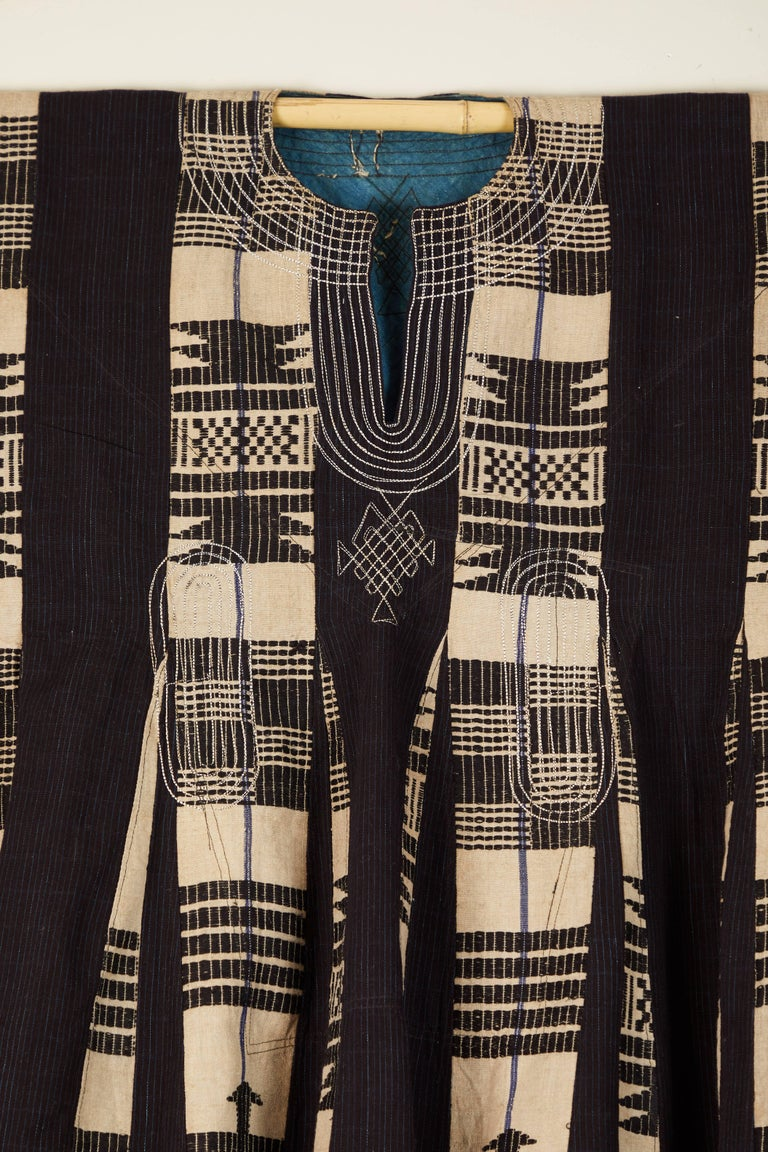 Traditional man's cotton tunic made from handwoven, supplementary weft narrow strips sewn together.