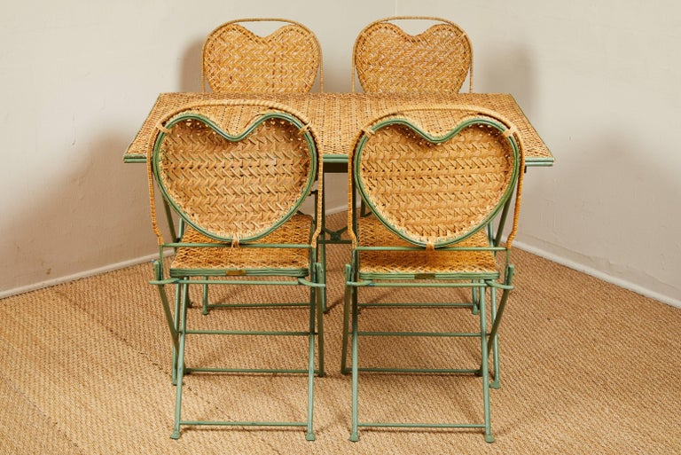 Patented folding table and chair set made in USA by Un Jardin en Plus. See image 12 for metal tag. Heart shaped caned backs on the chairs. Slightly distressed turquoise blue painted metal.