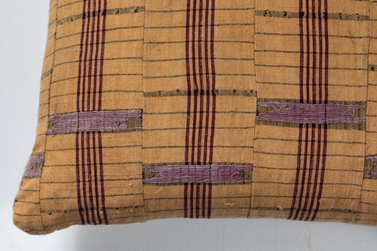 Pillow made using vintage Asoke fabric. Handwoven in Nigeria by the Yoruba peoples. Long strips of cotton and raw silk made on narrow looms and sewn together. Natural linen back. Invisible zipper and feather and down fill.