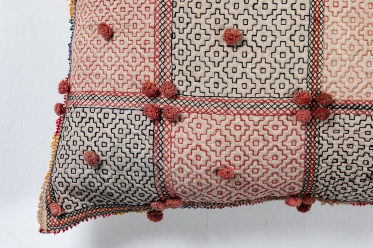 Vintage cotton storage bag reconfigured into a pillow. Geometric embroidery pattern and pompoms. Natural linen back, invisible zipper enclosure and feather and down fill.