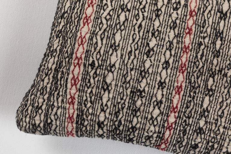 Vintage cotton on cotton embroidery producing a heavy quilted effect. Shades of black and white and (red). Zig zag and geometric stripes. Made as a tunic in Nuristan, Afghanistan. Black linen backing. Feather and down fill, invisible zipper