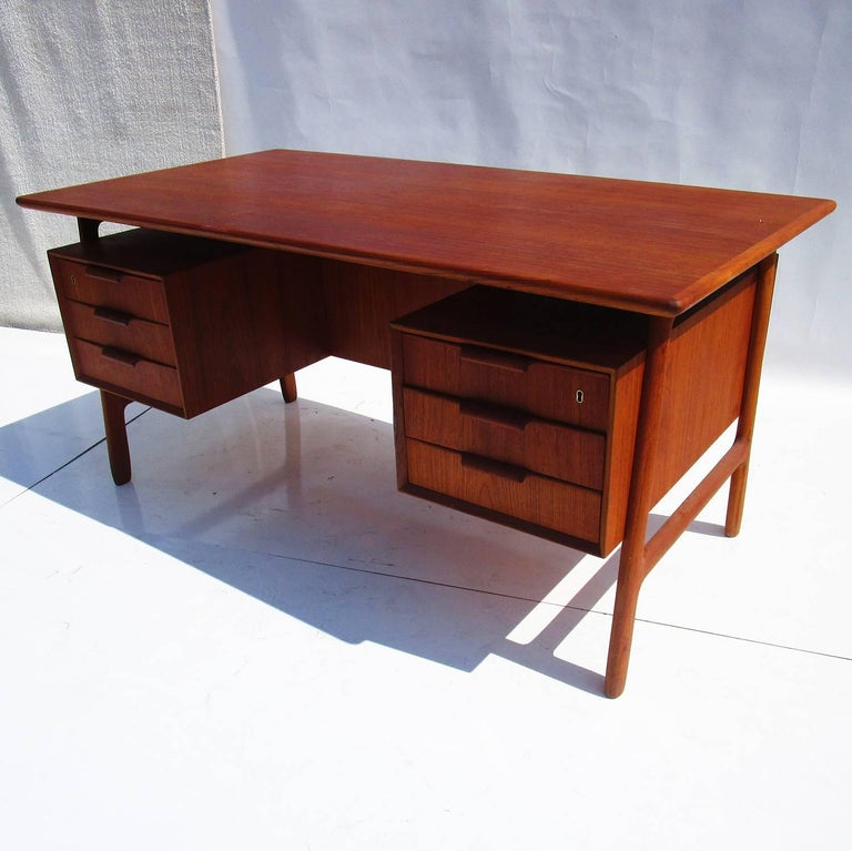 "A Classic and clean design by Gunni Omann of Denmark. The desk features an opening compartment and two bookcase areas on the front side, as well as multiple drawers. This style has a ""floating"" top as an added design feature. Previously refinished,"