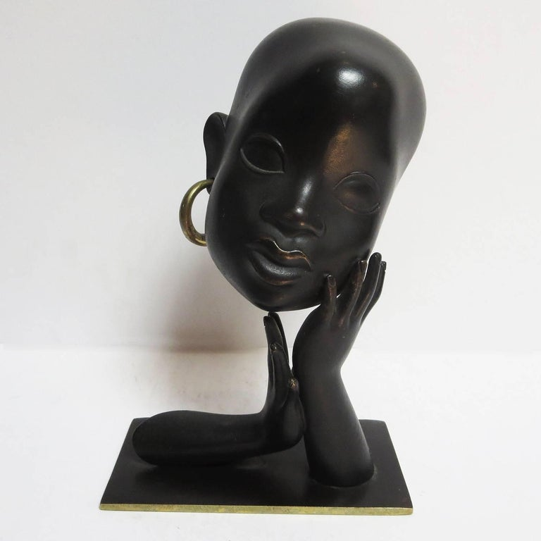 This lovely African sculpture was created by Karl Hagenauer of Vienna Austria. There was a fascination with African fashion and design throughout Europe in the Art Deco period. The sculpture is cast bronze, with a blackened patina. The original
