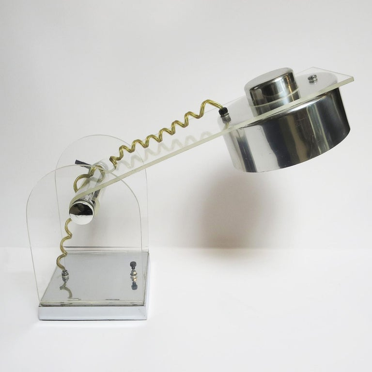 A very stylized lamp from the midcentury era. The body is polished acrylic Lucite, mounted on a chromed steel base. The shade is polished aluminium. The upper half of the lamp is adjustable up or down. The lamp works fine, and shows minor wear of