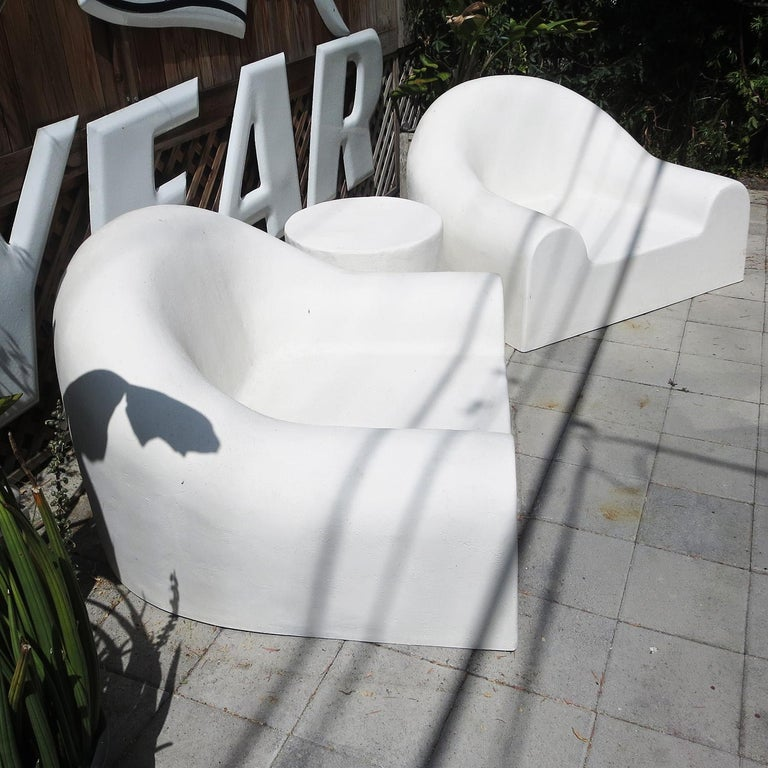 This 1970s design by Michael Taylor is a mix of Flintstones and Futurism. The chairs appear to be poured concrete, but are actually a fiberglass material. There is a textured painted finish, which adds to the stone feeling. The chairs originally