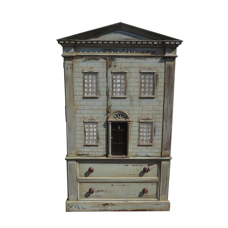 This charming cabinet was designed to resemble a large building. The exterior surfaces are hand painted and show intended wear. The top section lifts off the drawers and base for easy moving. The top opens to reveal removable shelves, while the