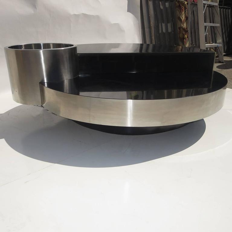 This fantastic design was introduced in 1970 by Mario Sabot of Italy. Designer Willy Rizzo created a number of designs for the company, but this stands out as the most unique. The circular table is wrapped in brushed stainless steel, with black