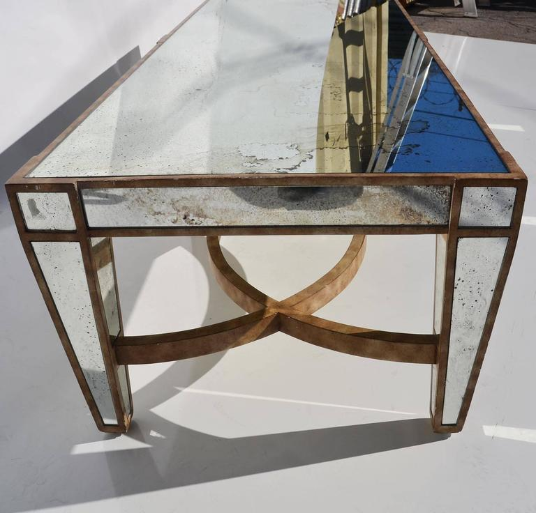 This impressive table is made of multiple panels of aged mirror, set into a painted wood table. The overall condition is quite nice, with natural intended aging.