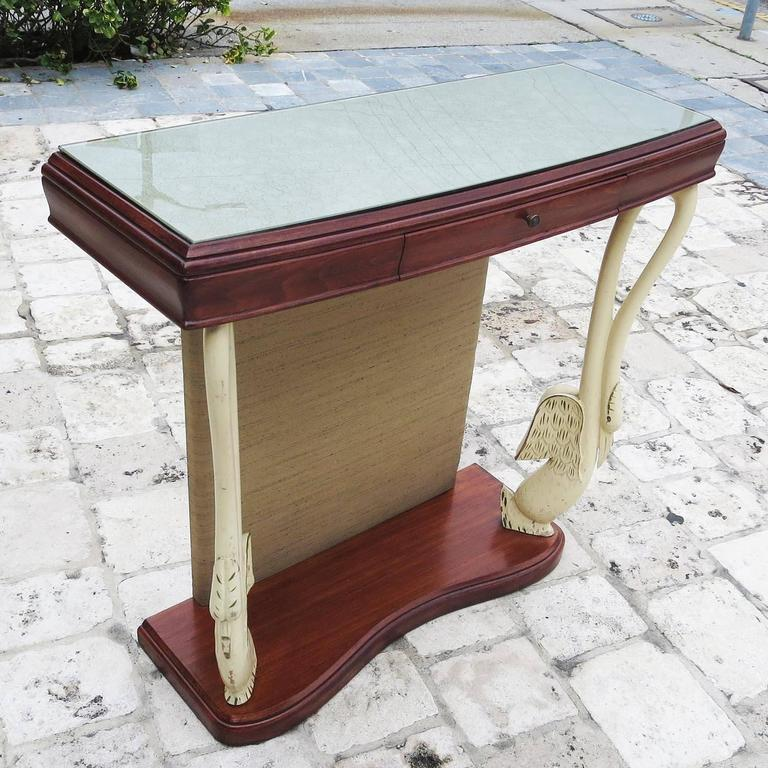 This charming table features clean lines and a petite scale. The woods are a combination of painted and natural finishes. The centre panel is wrapped in original fabric. The inlaid top glass panel has an original finish of reverse paint in a