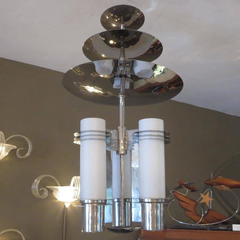 An incredibly stylized lamp that would have been found in a 1930s theatre or skyscraper lobby. The lamp has been re-plated and rewired, and looks terrific. The top disc slides down for ceiling mounting, then raises up to cover the ceiling mount.