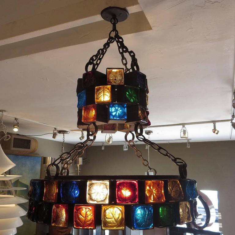 This fantastic lamp was designed by Feder of Mexico, circa 1960s. Each of the 69 steel cubes houses a colored molded glass face with an impressed leaf pattern. This is the largest and most elaborate chandelier we have encountered from the company.