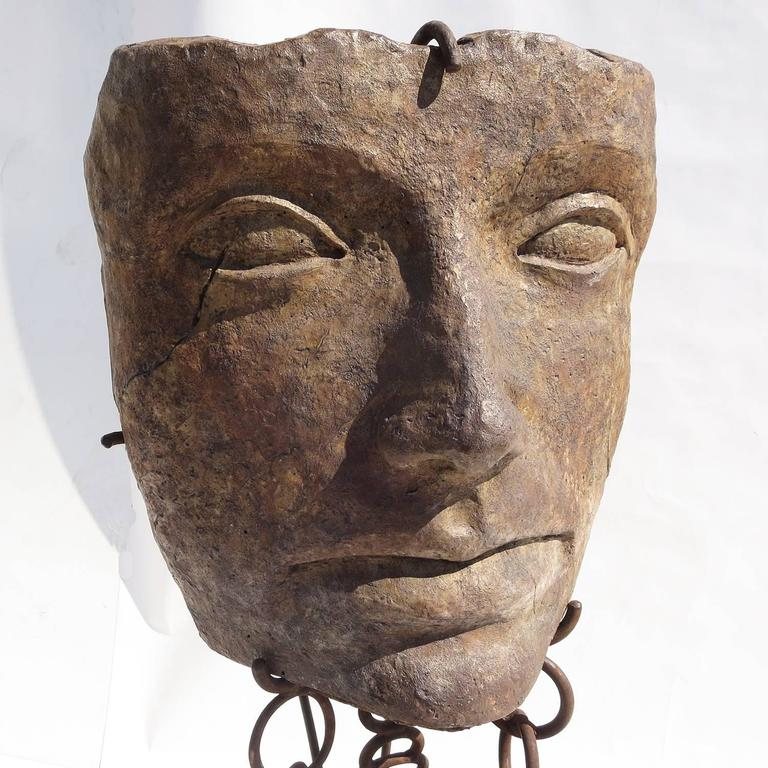 This amazing sculpture seems to have been retrieved from the depths of the ocean, suspended in mid air by heavy chains. The head, by an unknown artist, is a sculpted and glazed ceramic material, resembling carved stone. There is a hallmark stamp by