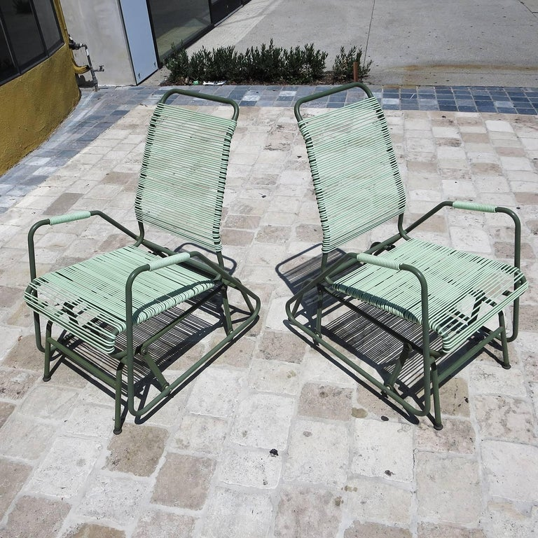 This great pair are incredibly comfortable, and in amazing original condition. The mint colored rubberized webbing is supple and unbroken, and the painted frames are very clean. The chairs glide forward and back smoothly, and they look terrific.