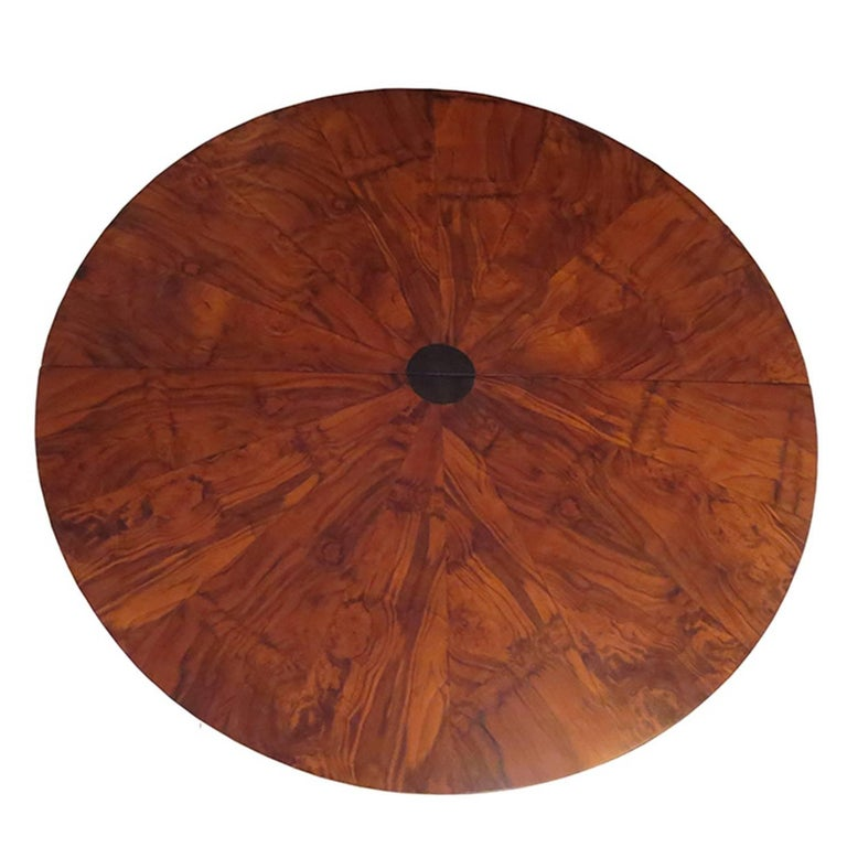 "This incredible dining table was designed by Paul Evans in the 1970s as part of the ""Cityscape"" line. The top is a highly figured burled wood grain in a sunburst pattern with an ebonized circular center. With the extension in place, the center"