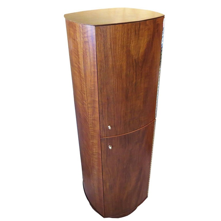 This cabinet is one of the more unusual designs we have encountered. The tall tower revolves on a fixed base. On one side is a bank of drawers and an upper cabinet with shelving. It revolves to reveal a second side which consists of two elongated