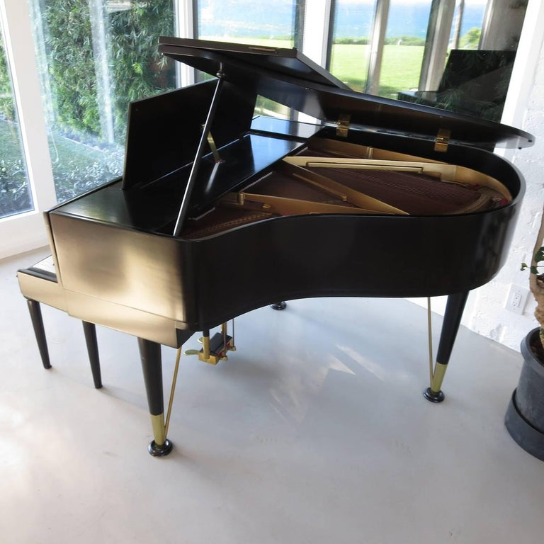 This lovely piano was designed by Torben Christensen for the Andreas Christensen piano company of Denmark in 1955. The lines are classic Mid Century Modern, down to the brass tipped hairpin legs. The cabinet was refinished some time ago, and