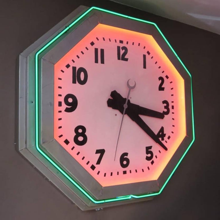 A beautiful example of moderne styling represented in this octagonal Deco neon clock. Easy to live with dark green glass forms the outside ring, the inside ring is red but hidden by the bezel so you see only the glow. There is a pull chain to turn