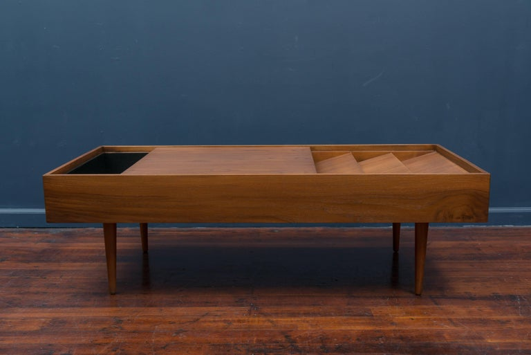 Early Milo Baughman design walnut magazine coffee table for Glenn of California. Unique sliding top that opens and closes compartments for magazines, remote controls etc.