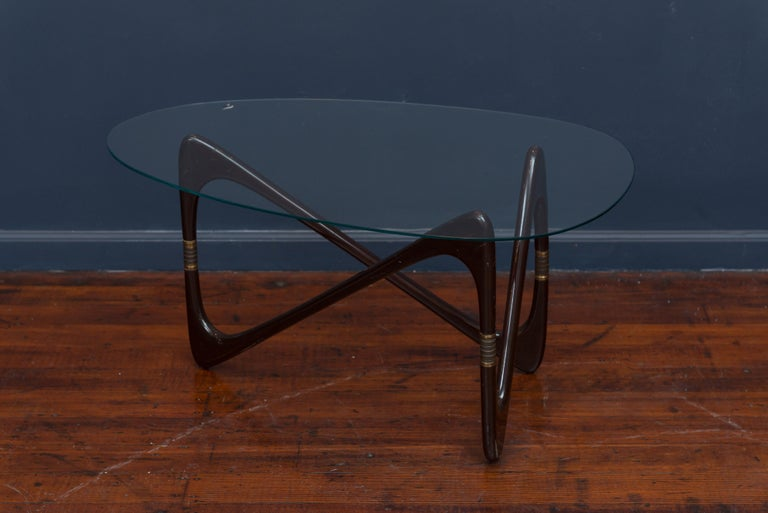 Cesare Lacca coffee table with a lacquered wood base, gilt metal mounts and original tear drop beveled glass top.