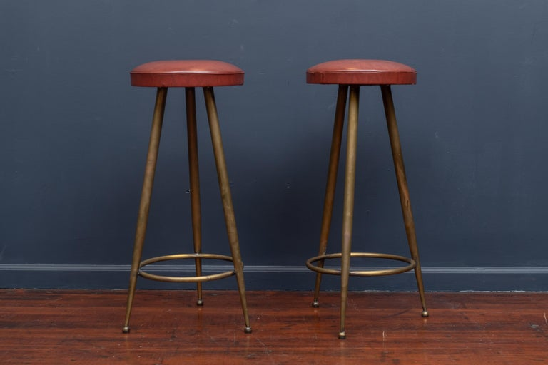 Pair of chic Italian brass bar stools with vinyl seat cushions, in very good vintage condition.