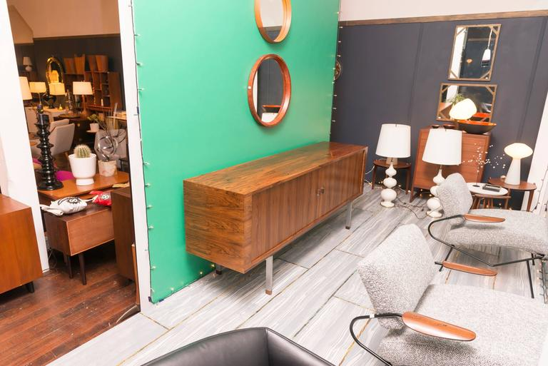 """Hans Wegner design """"President"""" credenza for Ry Mobler, Denmark.  Perfectly refinished figural rosewood case floating on a stainless steel base capped off with rosewood block feet. The tambour doors disappear into the body to reveal adjustable oak"""