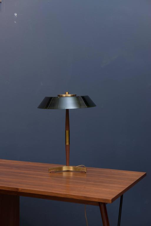 Fog & Mørup manufactured table lamp made from teak and brass with a green glass shade. Three or four flea size chips to glass shade edge.