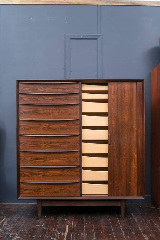 High quality construction and design rosewood dresser with eight drawers on the left hand side and nine inside of the tambour door compartment. Newly cleaned and waxed and all drawers and doors operate smoothly, labeled.