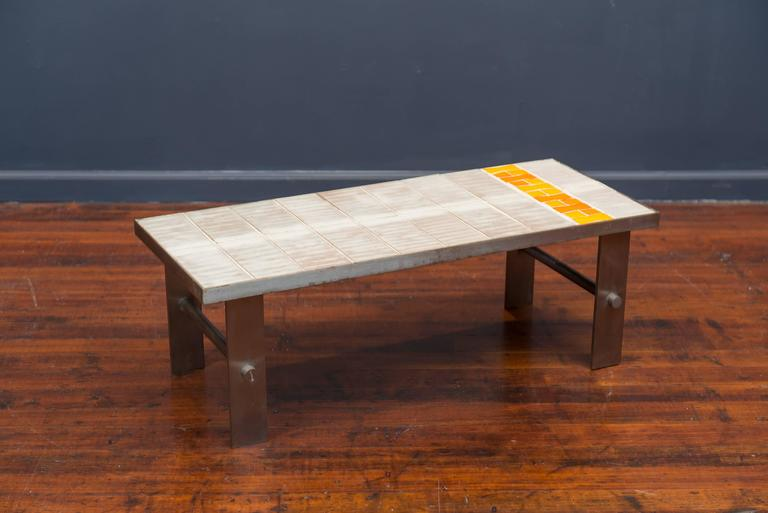 French coffee table made with a brushed steel frame and legs and a ceramic tile inset top. Very good vintage condition.
