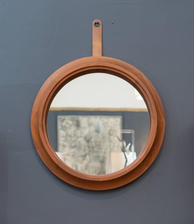 High quality design Danish modern teak wall mirror with a leather strap.