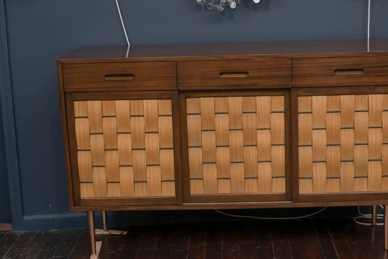 Elegant design by Edward Wormley for Dunbar Furniture Company, Berne Indiana. Perfectly refinished mahogany case with three top drawers and sliding woven front doors on tapering polished legs. Fitted interior comprises six drawers and two adjustable