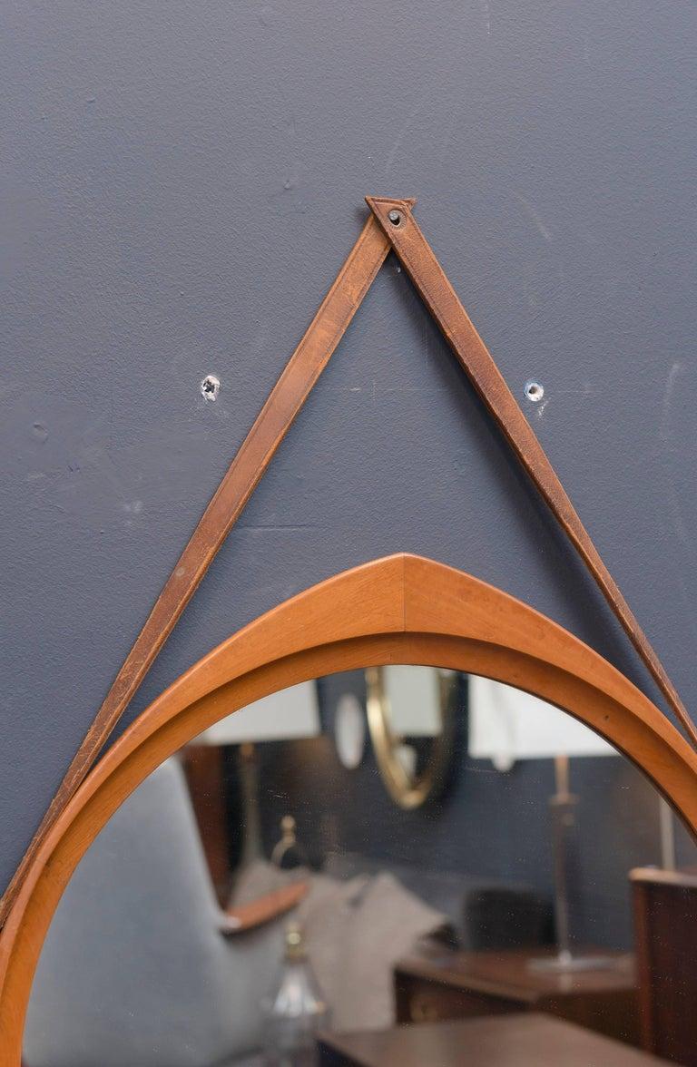 Unusual shape Scandinavian teak wall mirror with leather straps.