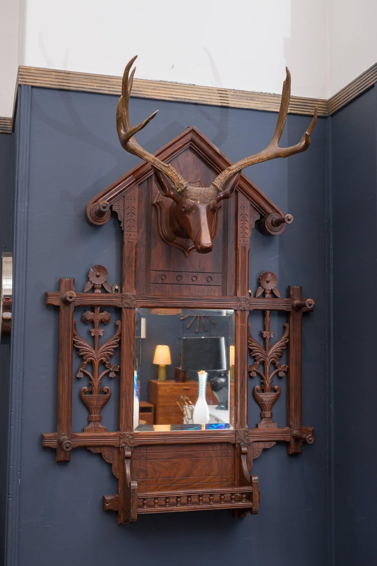 Black Forest handmade hall tree made from mahogany and rosewoods. Dramatic wooden carved deer head with antlers and floral carvings and hooks. Old repair to center of frame, original mirror plate.